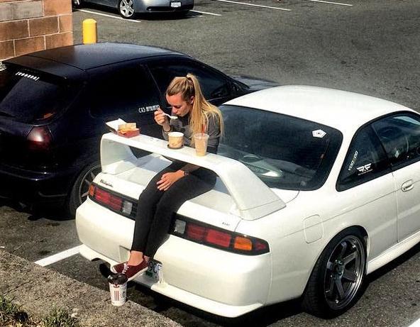 девушка обедает за автомобильным сполером